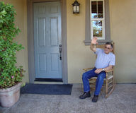 Senior Man Waving. Senior Man sitting in rocking chair on front porch waving Royalty Free Stock Images