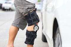 Senior man wear knee support brace on leg standing at the car parking lot, Medical and healthcare concept royalty free stock image