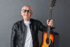 Senior man in leather jacket and sunglasses standing isolated on gray holding guitar looking camera positive royalty free stock photo