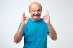 Senior man wearing a blue outfit doing a double ok gesture with his hands. Royalty Free Stock Photos