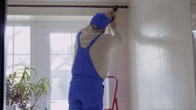 Senior man wearing blue protective coveralls repairing cornice over the window. Mature man wearing blue protective overalls stand on the ladder and repairs the stock video footage