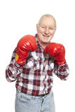 Senior man wearing boxing gloves smiling. On white background Stock Photo