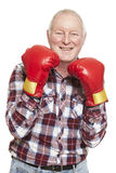 Senior man wearing boxing gloves smiling. On white background Stock Photos