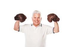 Senior man wearing boxing gloves smiling on white Stock Photos