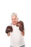 Senior man wearing boxing gloves smiling on white Stock Images