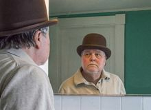 Senior man wearing a brown derby in the bathroom mirror. Older man wearing a brown derby and looking at himself in bathroom mirror stock photography