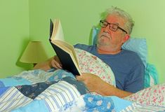 Senior man reading in bed. royalty free stock photo