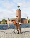 Senior man wearing old fashioned tweed suit holding a high wheeler bicycle in front of Stockholm City Hall stock photo