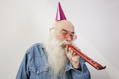 Senior man wearing party hat while blowing horn against gray background Stock Images