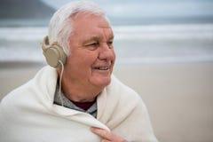 Senior man wearing shawl and listening music on headphones Royalty Free Stock Image