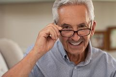 Senior man wearing spectacles. Portrait of happy mature man wearing spectacles and looking at camera. Old man smiling with glasses at home. Closeup face of elder royalty free stock image