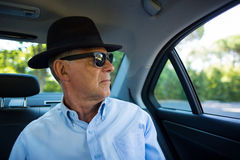 Senior man wearing sunglasses and hat in car. Senior man wearing sunglasses and hat while sitting in car Stock Image
