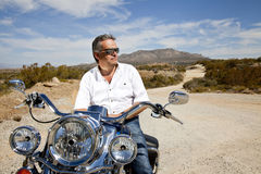 Senior man wearing sunglasses on motorcycle in desert Royalty Free Stock Photography