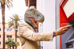 Senior man wearing t-rex dinosaur mask withdraw money from bank cash machine with debit card - Surreal image of half human royalty free stock photo