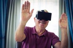 Senior man wearing virtual glasses. At home Stock Image