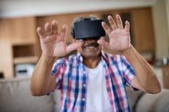 Senior man wearing virtual reality headset in living room Royalty Free Stock Image