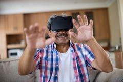 Senior man wearing virtual reality headset in living room Royalty Free Stock Photo