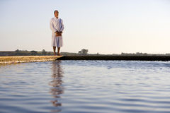 Senior man wearing white bath robe, standing outdoors by swimming pool, eyes closed Royalty Free Stock Images