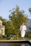 Senior man wearing white bath robe, standing outdoors by swimming pool, eyes closed Stock Photo