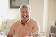 Senior Man At A Wedding. Happy senior man at a wedding. He is sitting at a table, laughing with guests out of the frame stock photography