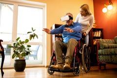 Senior man in wheelchair having fun while using VR stock photos
