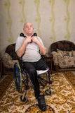 Senior Man in Wheelchair Holding Dumbbells at Home Stock Photography