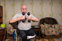 Senior Man in Wheelchair Lifting Dumbbells at Home Royalty Free Stock Photo