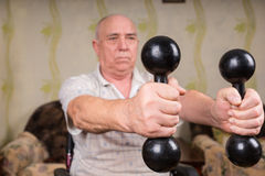 Senior Man in Wheelchair Lifting Dumbbells at Home Stock Image