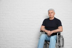 Senior man in wheelchair near brick wall indoors. Space for text stock photos
