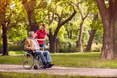 Senior man in wheelchair in the park with daughter Royalty Free Stock Images
