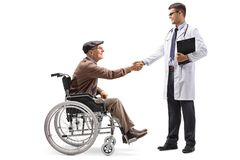 Senior man in a wheelchair shaking hands with a young male doctor royalty free stock images
