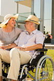 Senior man in wheelchair smiling on his wife Royalty Free Stock Images