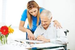 Senior man in wheelchair solving mazes Royalty Free Stock Photo
