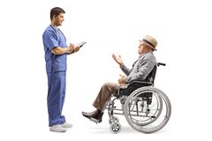 Senior man in a wheelchair talking to a young male doctor. Full length profile shot of a senior men in a wheelchair talking to a young male doctor isolated on royalty free stock photo