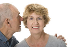 Senior man whispering in his wife's ear. Loving senior couple on white background royalty free stock photo