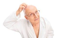 Senior man in a white bathrobe checking his hair Royalty Free Stock Images