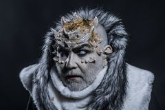 Senior man with white beard dressed like monster. Dark arts concept. Demon on black background, close up. Man with Stock Image