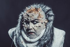 Senior man with white beard dressed like monster. Dark arts concept. Demon on black background, close up. Man with royalty free stock photography