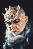 Senior man with white beard dressed like monster. Demon on black background, close up. Man with thorns or warts in fur royalty free stock image