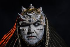 Senior man with white beard dressed like monster. Man with thorns or warts, face covered with glitters. Fantasy concept. Demon with golden hood on black Royalty Free Stock Images