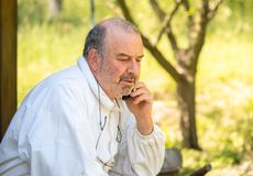 Senior man in white dress talking on the phone. In the garden stock image