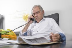 Senior man with white shirt phoning Royalty Free Stock Images