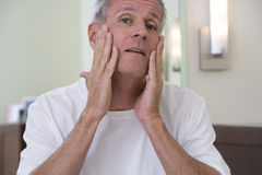 Senior man, in white t-shirt, applying moisturiser to face in bathroom, close-up, front view, portrait Royalty Free Stock Photo