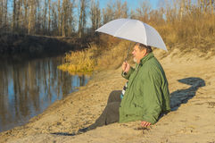 Senior man with white umbrella sitting on a river beach Stock Image