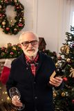 Senior man with wine at christmastime. Senior man holding wine bottle and wine glass at christmastime royalty free stock photos
