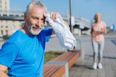 Senior man wiping sweat from the forehead with towel. Getting some rest. Handsome senior men sitting on the bench and wiping sweat from the forehead with towel royalty free stock photos
