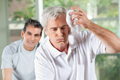 Senior man wiping sweat of his Royalty Free Stock Images