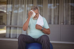 Senior man wiping sweat off his face with towel Stock Photo