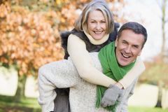 Senior man and woman. Senior man giving woman piggyback ride through autumn woods