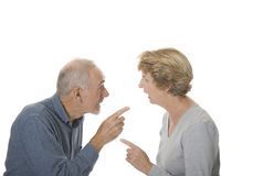 Senior man and woman arguing. Old man and elderly woman pointing fingers at one another during an argument. Isolated on white stock photos